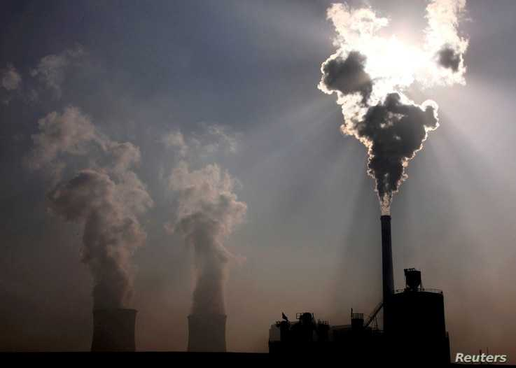 FILE PHOTO: A coal-fired power plant can be seen behind a factory in China's Inner Mongolia Autonomous Region, October 31 ...
